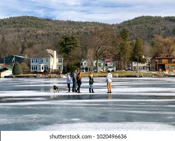 LAKE GOERGE, NY - JANUARY 28, 2018: People and their dog standing on frozen Lake George in New York with snow and ice covered lake surface with Adirondack mountains in the background in winter.