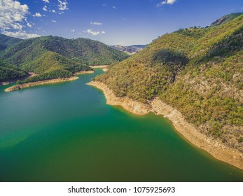 Lake and green forested hills on bright summer day
