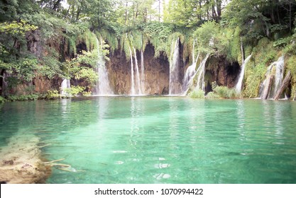 Lake with green transparent water and a waterfall in the background in Plitvice