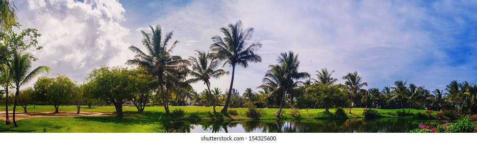 Lake in green tropical forest. tropical park - travel background. Golf Course in Tropical Paradise. Summertime holyday in Dominican Republic, Caribbean. Golf Course on Green Ocean Shore. Luxury Resort