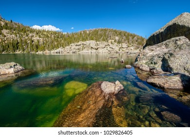 Lake Haiyaha with rocks and mountains in snow around at autumn. Rocky Mountain National Park in Colorado, USA.