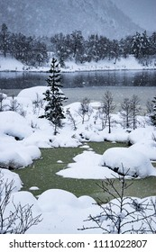 Lake half frozen in winter snowing