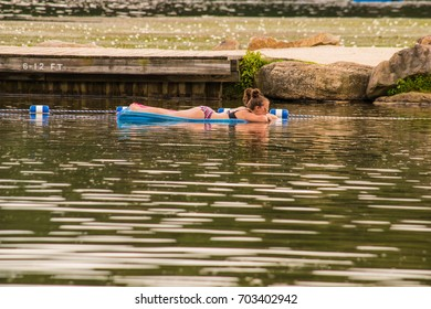 Lake Harmony, PA - August 24, 2017: Two young girls enjoy floating on inflatable rafts which is one of the relaxing activities one can participate in at Lake Harmony.
