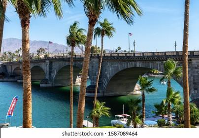 Lake Havasu, Arizona / USA - 20 Oct 2019: View of London Bridge through tall palm trees and across azure blue water.