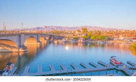 Lake Havasu City, AZ 8-30-2021: London Bridge and surrounding English Village at sunset. Boat dock of the Heat Hotel to the front. Twilight colors reflect beautifully onto buildings on the other side.