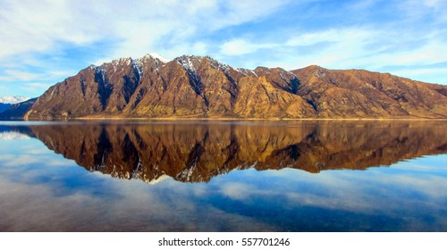 Lake Hawea, New Zealand - with snow-capped mountains reflecting in the surface of the calm lake, taken on a clear, winter's day from the lake shore.