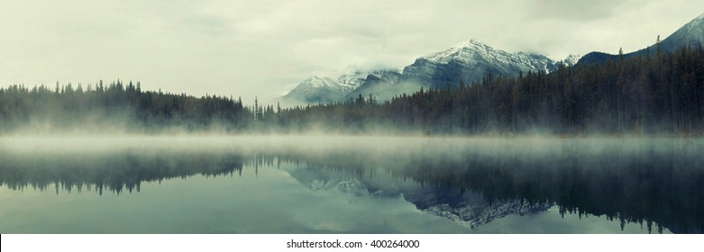 Lake Herbert panorama in a foggy morning with glaciers mountain and reflection in Banff National Park, Canada