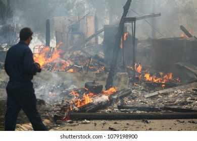 Lake Hodges, CA/USA - Oct 23, 2007: A photographer walks by a home was burned by the Harris fire around Lake Hodges, California. Over 200 homes were lost to the blaze.