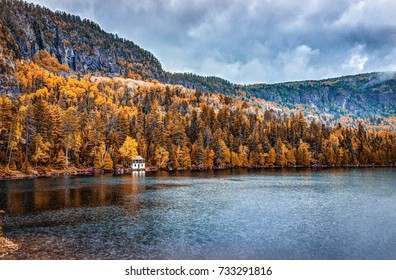 Lake house in autumn landscape by water during rainy cloudy day in Quebec, Canada with stormy clouds and dark weather