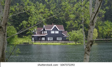 A lake house between the trees in breathtaking nature. The house in the greenery near the lake. Cennet Gol (Paradise Lake), Turkey. Reflected on water. Country side, forest and lake with house.