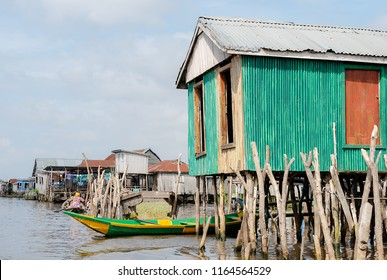 Lake house and boat. Benin lake Nokoué lifestyle African villager living on house in water. Trading with barter system. West-Africa life in Benin living with boats on the lake.