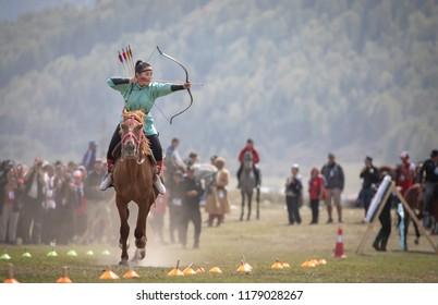 Lake Issyk-Kul, Kyrgyzstan, 6th September 2018: Woman competing in archery on horseback game