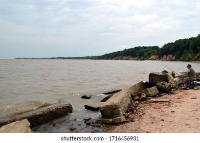 Lake Khanka, Kamen-Rybolov, Primorsky Krai, Russia - July 7 2018:   Famous Khanka lake on the border between Russia and China. Fisherman fishing on the shore on a sunny day