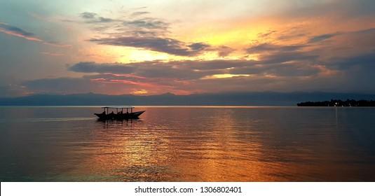Lake Kivu, Rwanda; A ferry boat sailing in the water - sunset at sea. Popular tourist spot in Rwanda, East Africa.