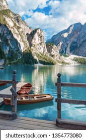 Lake Lago di Braies in Dolomiti mountains, South Tyrol, Italy. Dock with romantic old wooden rowing boats on lake. Amazing view of Lago di Braies (Braies lake, Pragser wildsee) in sunset light.