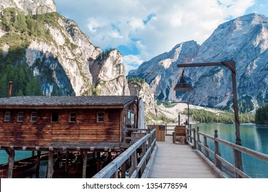 Lake Lago di Braies in Dolomiti mountains, South Tyrol, Italy. Scenic view from the romantic wooden dock over water. Amazing view of Lago di Braies (Braies lake, Pragser wildsee) at sunset light.