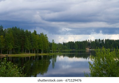 Lake landscape with forest in a cloudy summer day. Mirror and grass.