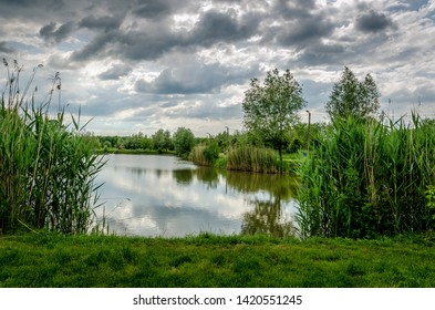 Lake landscape with green bushes and trees and dark cloudy sky