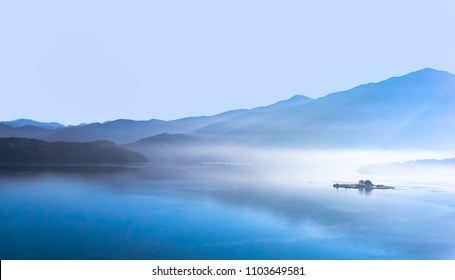 Lake landscape in morning smog with reflection of the mountains on the lake