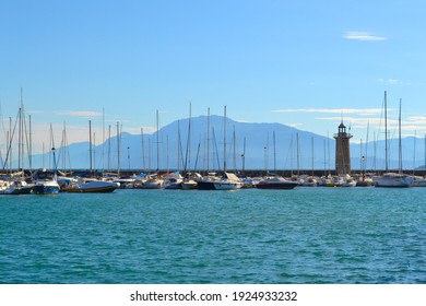Lake landscape with sailboats, lighthouse, blue water, white clouds, mountains in haze. Lake Garda in Italy. Vacation concept