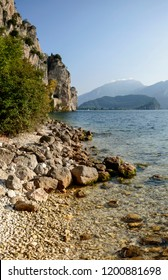 lake landscape with small shingle beach and clear water under vertical rock walls , shot in bright fall light near Riva del Garda, Trento, Italy