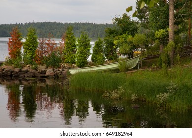 Lake landscape in a summer cloudy day. Landscape with green boat.