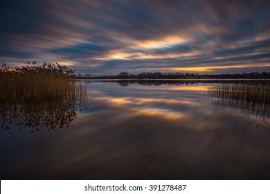 Lake landscape sunset photographed on long exposure. Polish lake in Mazury lake district.