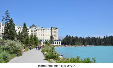 LAKE LOUISE, AB / CANADA - JULY 27, 2017:  Tourists walk along the end of the trail near Fairmont Chateau Lake Louise hotel.