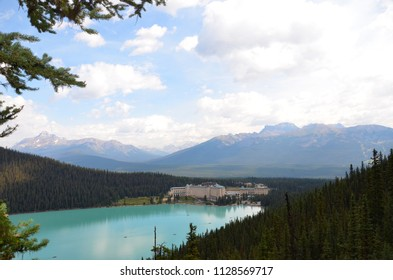 LAKE LOUISE, AB / CANADA - JULY 28, 2017:  The Fairmont Chateau Lake Louise, seen from an overlook in the nearby forest, was conceived by the railroad to entice tourists to the Canadian Rockies.