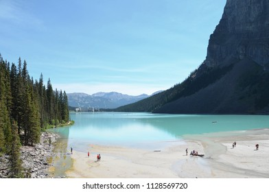 LAKE LOUISE, AB / CANADA - JULY 26, 2017:  Tourists explore the end of Lake Louise opposite the Fairmont Chateau Lake Louise hotel.