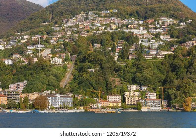 Lake Lugano and buildings on the foot of the Monte Bre mountain in Switzerland, view from the city of Lugano in the Swiss canton of Ticino at the middle of October.
