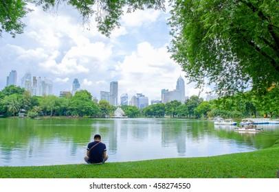 Lake Lumpini National Park with city landscape background in Bangkok, Thailand