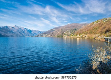 Lake Maggiore, view towards Colmegna, Maccagno and the Alps, province of Varese, Italy. To the right, the road and the railroad along the shore of Lake Maggiore
