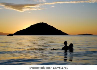 Lake Malawi, Malawi, 4/2/2007 Silhouette of a couple swimming in Lake Malawi at sunset, Malawi