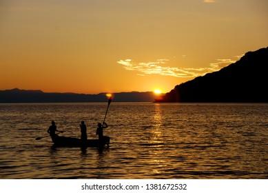 Lake Malawi, Malawi, 4/3/07  Three man on a canoe at sunset in silhouette on Lake Malawi, Malawi