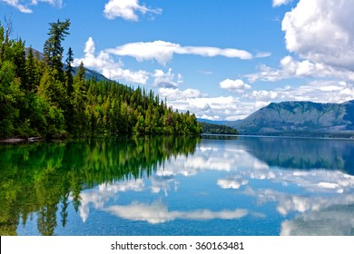 Lake McDonald located in Glacier National Park with water reflecting the clouds, mountains, and trees