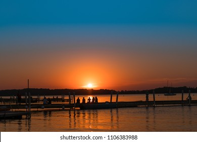 Lake Mendota. Memorial Union Terrace. Back to College. Students enjoying sunset. Party on Pier. University of Madison Wisconsin. Diverse kids hanging out. Silhouettes of students outside.
