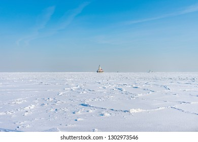 Lake Michigan in Chicago Frozen Over with Snow after a Polar Vortex with a Lighthouse in the distance