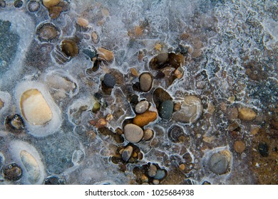 Lake Michigan at sunset in early February.  Here is sand and pebbles with ice and snow grains.