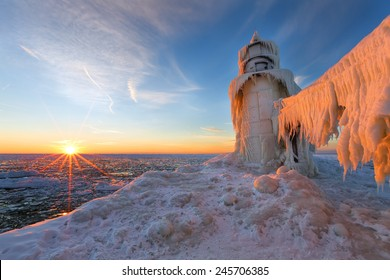 A Lake Michigan winter sunset illuminates the ices that encapsulates the St. Joseph northern pier.