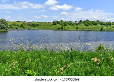 Lake in the middle of meadows with green lush grass on a sunny spring-summer day. Beautiful rural landscape with a pond. Panorama of the village of Uhroidy (Ugroedy) in the Sumy region (Ukraine)
