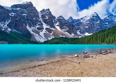 Lake Moraine in all his beauty. The beautiful blue lake and the surrounding mountains. A perfect beach in the foreground. Trees and mountains in the background