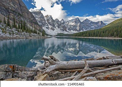 Lake Moraine glacial fed mountain pond with driftwood in forefront and mountain peaks in the background