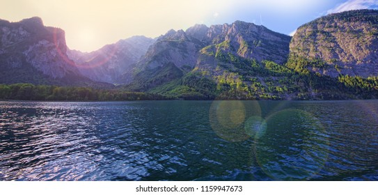 lake and mountain landscape with lens flare effect added from sun