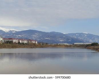 Lake and mountain range, buildings on shore