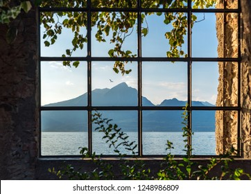 lake and mountain view in Torri del benaco through an ancient window. Verona, Italy