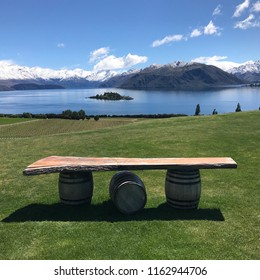 Lake and mountains background with background of wooden table on wine oak barrels stand on grass. Blue beautiful sky with some white clouds.