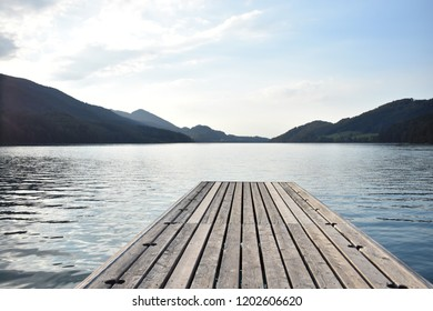 Lake with mountains on the background with wooden pier