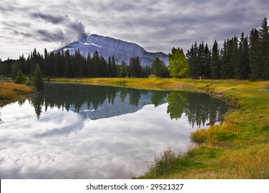 Lake in mountains surrounded by a wood and the cloudy sky
