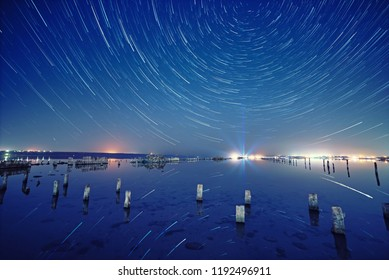 Lake at night with amazing starry sky and star tracks with reflections in the water. Natural outdors travel background.